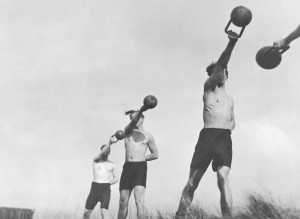 Group of young men exercising outdoors with weights (B&W)